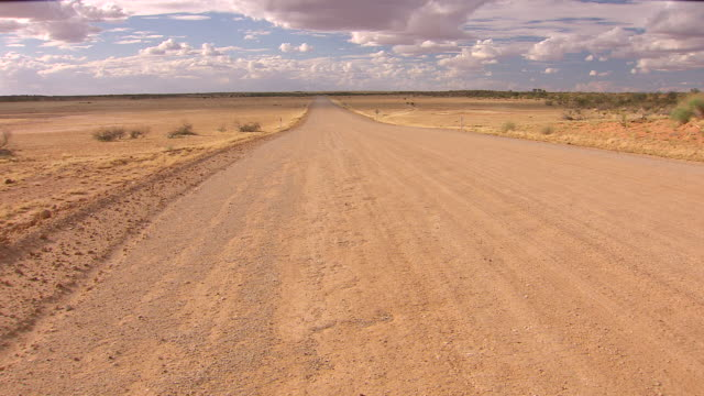 WS TU Jeep passing on outback road with cloudy sky / Tibooburra, New South Wales, Australia
