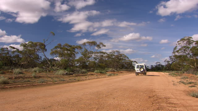 WS Jeep passing on outback road with trees and blue cloudy sky / Mildura, Victoria, Australia