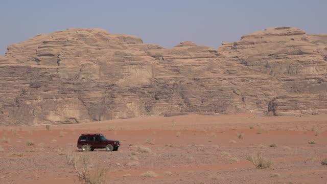 a jeep passing through wadi rum desert, jordan - sandstone stock videos & royalty-free footage