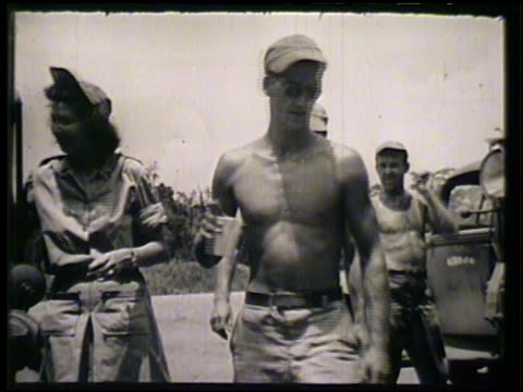 jeep pulling up near truck on road vs soldiers some topless taking drinks cracker snacks from female red cross member handing them out soldiers... - cracker stock videos and b-roll footage