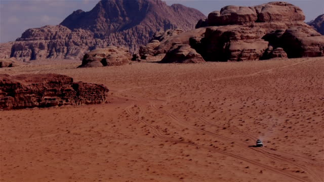 jeep seen from above in the wadi rum desert in jordan, middle east - ジープ点の映像素材/bロール