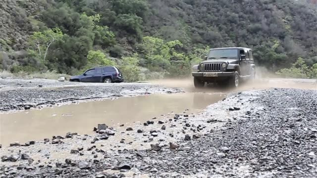 stockvideo's en b-roll-footage met jeep splashing into mud - onverharde weg