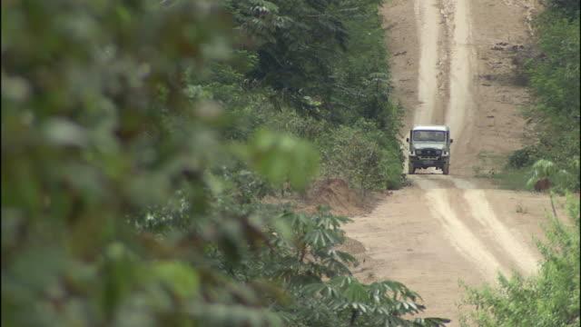 vídeos de stock, filmes e b-roll de a jeep travels along a dirt road in manaus, brazil. - estrada rural