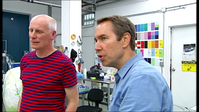 jeff koons and reporter in studio close shot of assistant sanding down artwork print out of popeye artwork on table tilt up to two assistants working... - popeye stock videos & royalty-free footage
