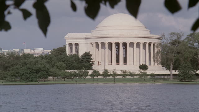 ws jefferson memorial across the tidal basin, with tree branch waving / washington, d.c., united states - jefferson memorial stock videos and b-roll footage