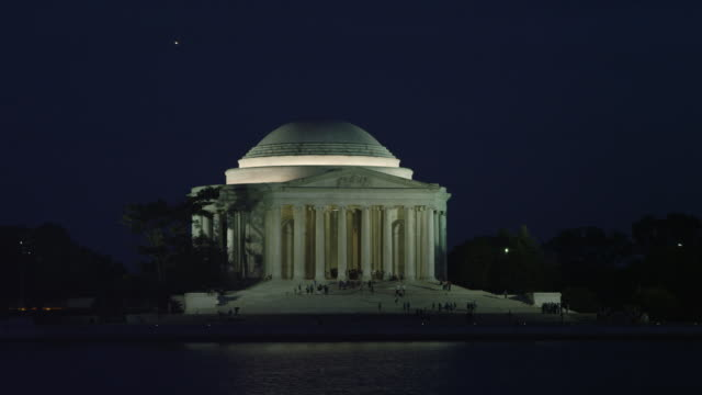 Jefferson Memorial by night, airplane passing at right of frame. Shot in 2012.