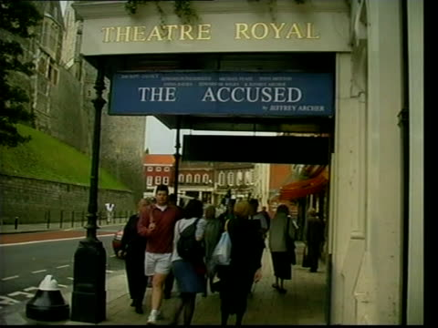 jeffrey archer play 'the accused' to close early itn lib london people along past theatre royal where play 'the accused' is being shown cs poster... - theatre royal stock videos and b-roll footage