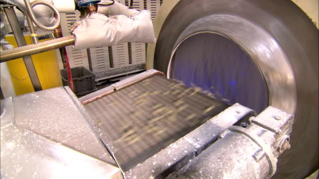 vídeos de stock e filmes b-roll de jelly beans speed down a conveyor belt into a spinning drum in a factory. - coinfeitos