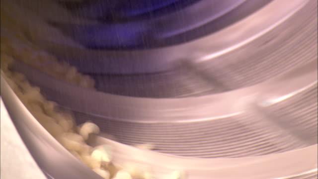 vídeos de stock e filmes b-roll de jelly beans tumble in a spinning drum in a factory. - coinfeitos