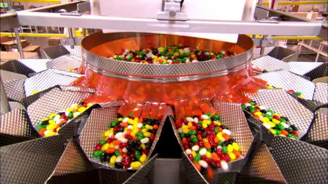 vídeos de stock e filmes b-roll de jellybeans pour into multiple chutes in a jelly bean factory. - coinfeitos