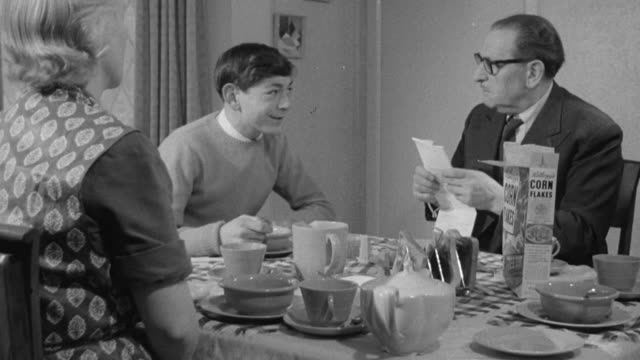 montage jenkins family eating breakfast, the son peeking at the community services bill and telling family about a civics lesson he had relating to the bill / united kingdom - matrum bildbanksvideor och videomaterial från bakom kulisserna