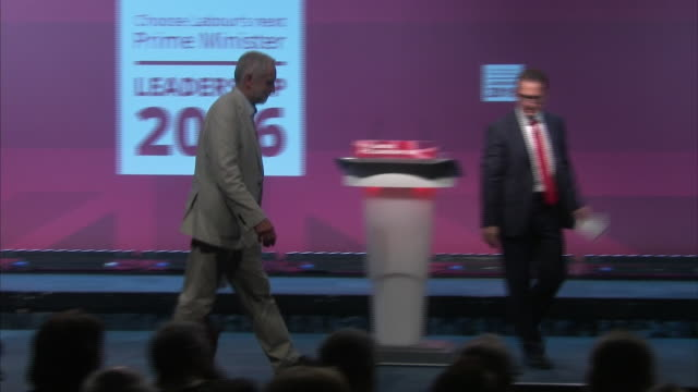 jeremy corbyn and owen smith walking off stage after a leadership debate followed by a zoomin on a sign asking people to choose labour's next leader - seguire attività che richiede movimento video stock e b–roll