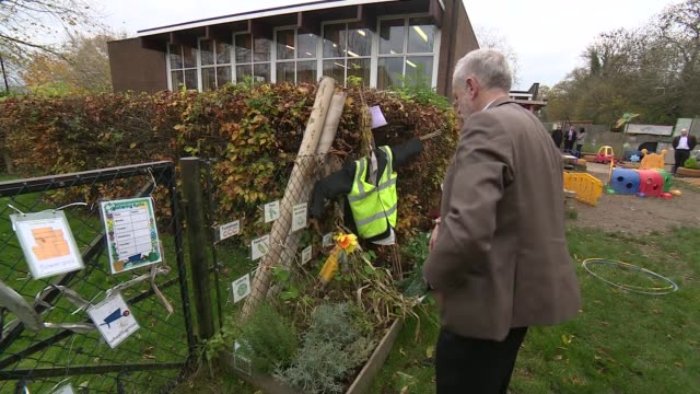 jeremy corbyn visits school on remembrance day ext jeremy corbyn teacher and others talk in nursery garden - remembrance day stock videos and b-roll footage