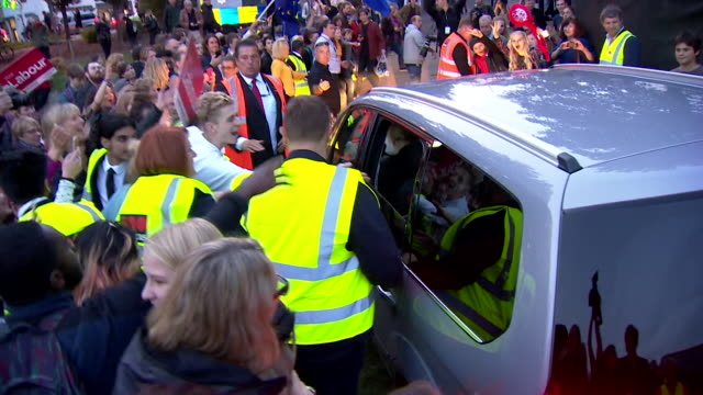 vidéos et rushes de jeremy corbyn's car is surrounded by fans and he is presented with red roses as he leaves an outdoor speech made during the labour party conference... - socialisme