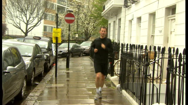culture department civil servant questioned england london jeremy hunt mp jogging towards along road in rain and into house - 政治家 ジェレミー ハント点の映像素材/bロール