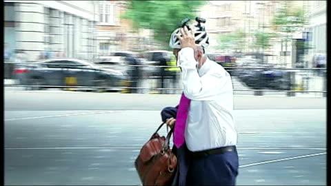 vídeos y material grabado en eventos de stock de jeremy paxman song and interview; england: london: ext jon snow along removing cycling helmet towards bbc broadcasting house - jeremy paxman