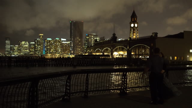 jersey city skyline, hoboken terminal, couple embracing - night time - ジャージーシティ点の映像素材/bロール