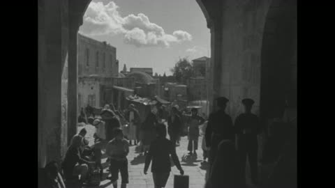 jerusalem / woman walking down street / people walking up and down narrow street / people passing back and forth through archway guarded by two... - パレスチナ文化点の映像素材/bロール