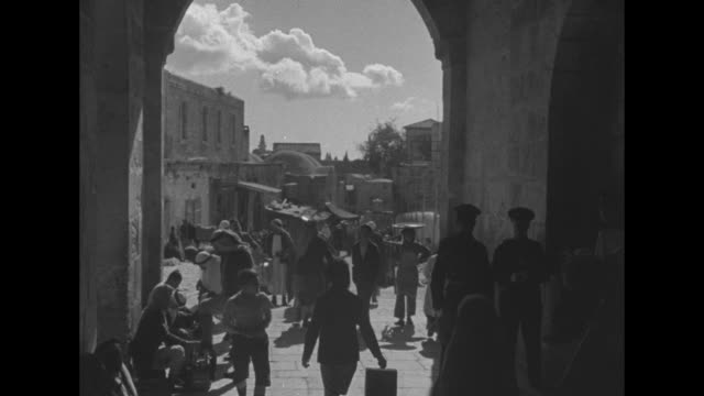 vídeos de stock e filmes b-roll de ws jerusalem / woman walking down street / people walking up and down narrow street / people passing back and forth through archway guarded by two... - palestino