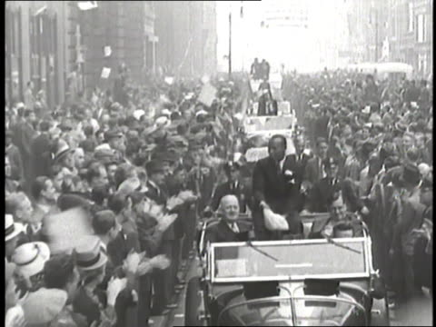 Jesse Owens rides in a convertible during a ticker tape parade in New York City