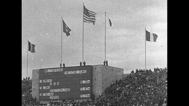 jesse owens runs down track and makes jump at 1936 summer olympics / stadium scoreboard with international flags above / women's 100meter dash... - salto in lungo video stock e b–roll