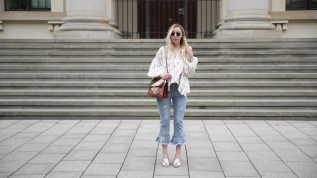 vídeos de stock e filmes b-roll de jessi quednau wearing a blouse with floral print from chicwish cropped denim jeans storets a brown chloe bag golden heeled slippers dorothy perkins... - blusa