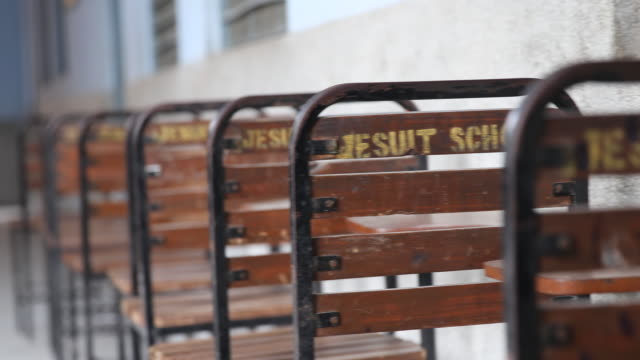 Jesuit school written on the back of school chairs seen in different focuses A girl walks in the background