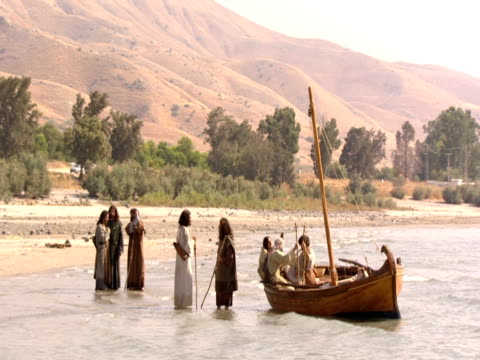 Jesus and his disciples gather by fishing boat in the Sea of Galilee.