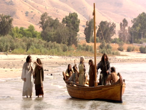 Jesus and his disciples wander on beach by the Sea of Galilee.