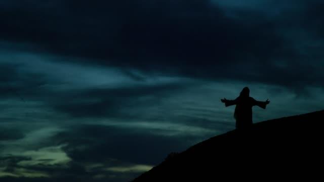 劇的な cloudscape の下で日の出/日没で屋外の丘の中腹に腕でひざまずいている間、シルエットのイエス・キリストは祈る - in silhouette点の映像素材/bロール