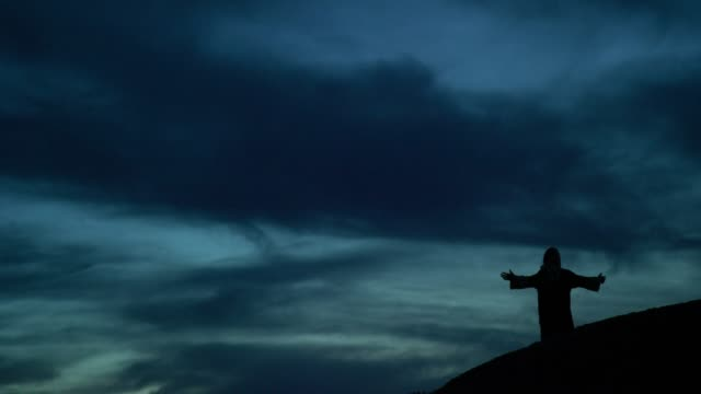jesus christ in silhouette walks down a hillside and drops to his knees to pray with arms out outdoors at sunrise/sunset under a dramatic cloudscape - jesus christ stock videos & royalty-free footage