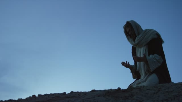 Jesus Christ Kneels on the Ground and Prays with Palms Out Outdoors at Sunrise/Sunset Outdoors in the Desert