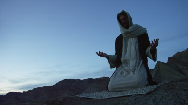 jesus christ kneels on the ground and prays with palms out outdoors at sunrise/sunset outdoors with a desert mountain range behind him - temptation stock videos & royalty-free footage