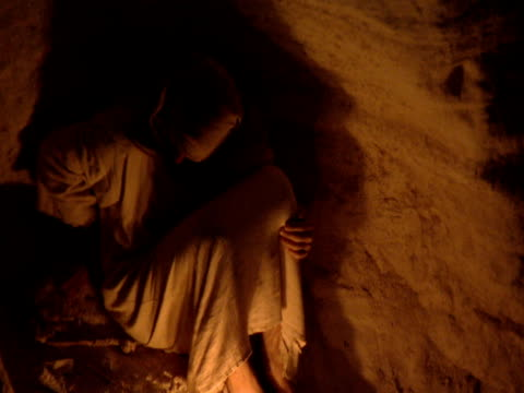 stockvideo's en b-roll-footage met jesus christ sits beside fire in cave - mid volwassen mannen
