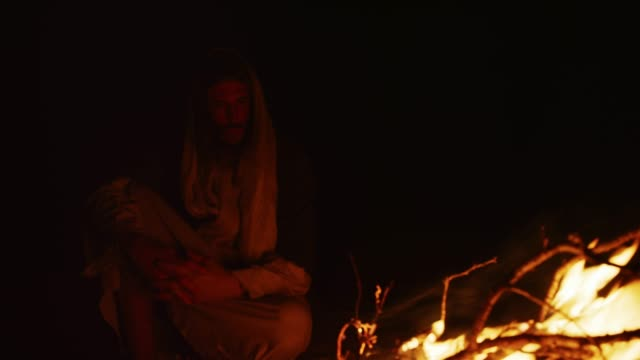Jesus Christ Sits by a Fire Outdoors at Night