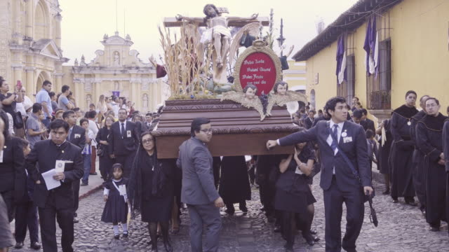 Jesus Christ statue carried by women dressed in black costume. Catholic parade at Antigua Guatemala during Lent Easter celebration.