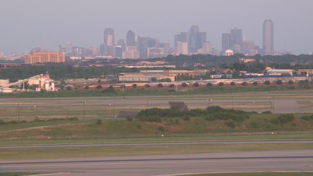 jet aircraft (mcdonnell douglas md-80) crosses frame after landing with city skyline in background/dfw international, dallas-fort worth, texas, usa - dallas fort worth airport stock videos & royalty-free footage