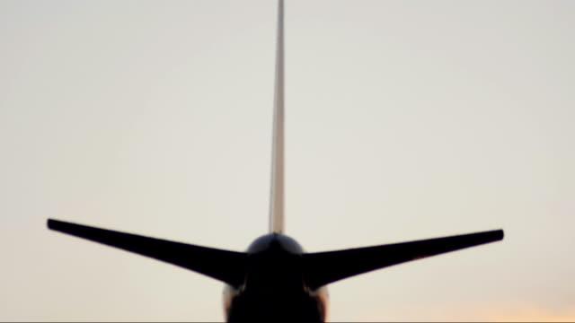 Avião a jato de aterragem durante o pôr do sol.
