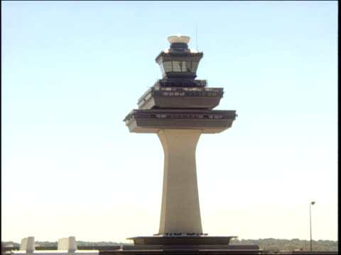 a jet airplane flies past the air traffic control tower at dulles international airport. - dulles international airport stock videos and b-roll footage