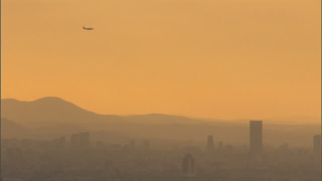 vidéos et rushes de jet airplane in distance descending over hazy almost silhouette of mexico city cityscape smoggy foggy pollution global warming earth air travel... - smog