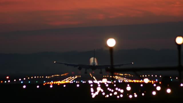 Jet airplane landing at sunset.