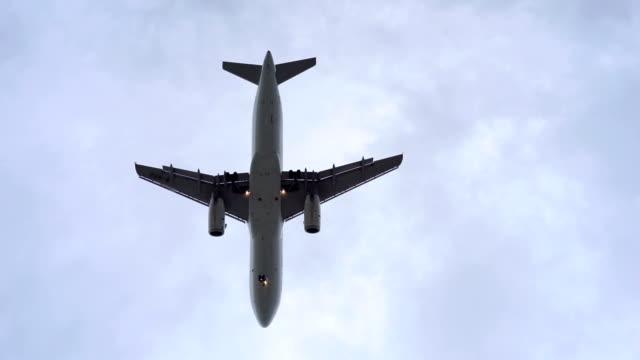 jet atterraggio di aeroplano passa sopra la testa - panoramicare verticalmente video stock e b–roll