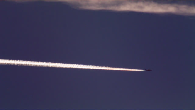 A jet airplane leaves a contrail as it flies across a summer sky.