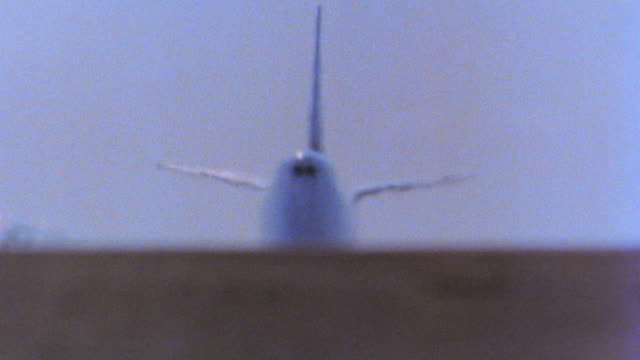 747 jet coming toward camera taking off from runway with heat waves in front of aircraft / tilt up