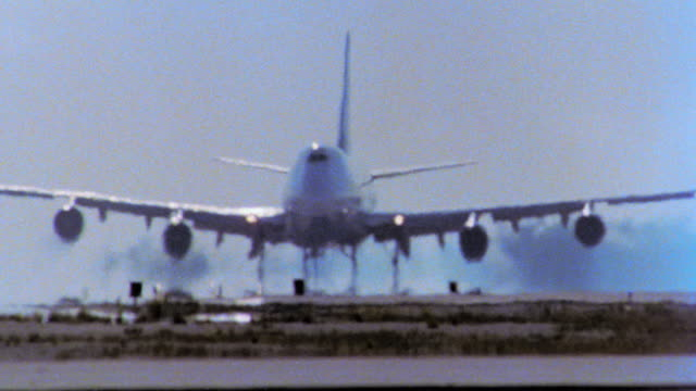 PAN 747 jet coming toward camera taking off from runway with heat waves in front of aircraft / tilt up