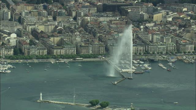 AERIAL Jet d'Eau fountain on lake Geneva and cityscape, Geneva, Switzerland