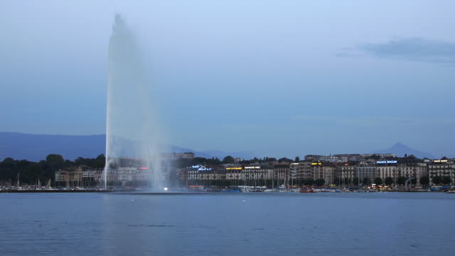 t/l ws jet d'eau on lake geneva, dusk to night, geneva, switzerland - fountain stock videos and b-roll footage