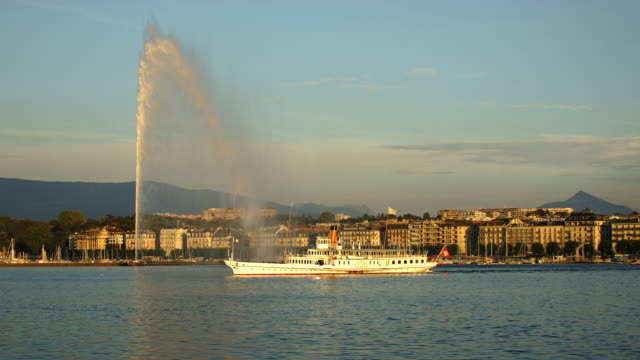 T/L WS Jet d'Eau on lake Geneva with ships passing in foreground, sunset, Geneva, Switzerland