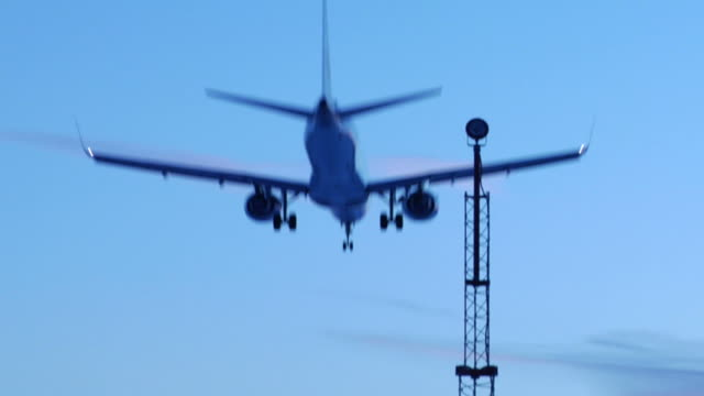 jet landing at dusk (hd video) - air traffic control tower stock videos and b-roll footage