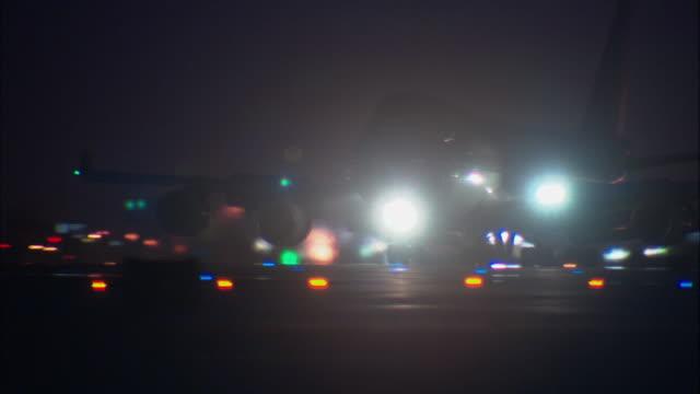 vidéos et rushes de ms, jet landing on tarmac at night, los angeles international airport, los angeles, california, usa - phare avant de véhicule